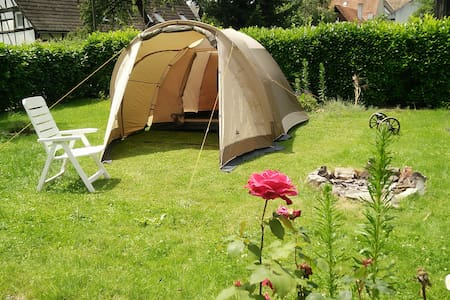 Zelt im Garten mit Lagerfeuer umgeben von Rosen - Tält