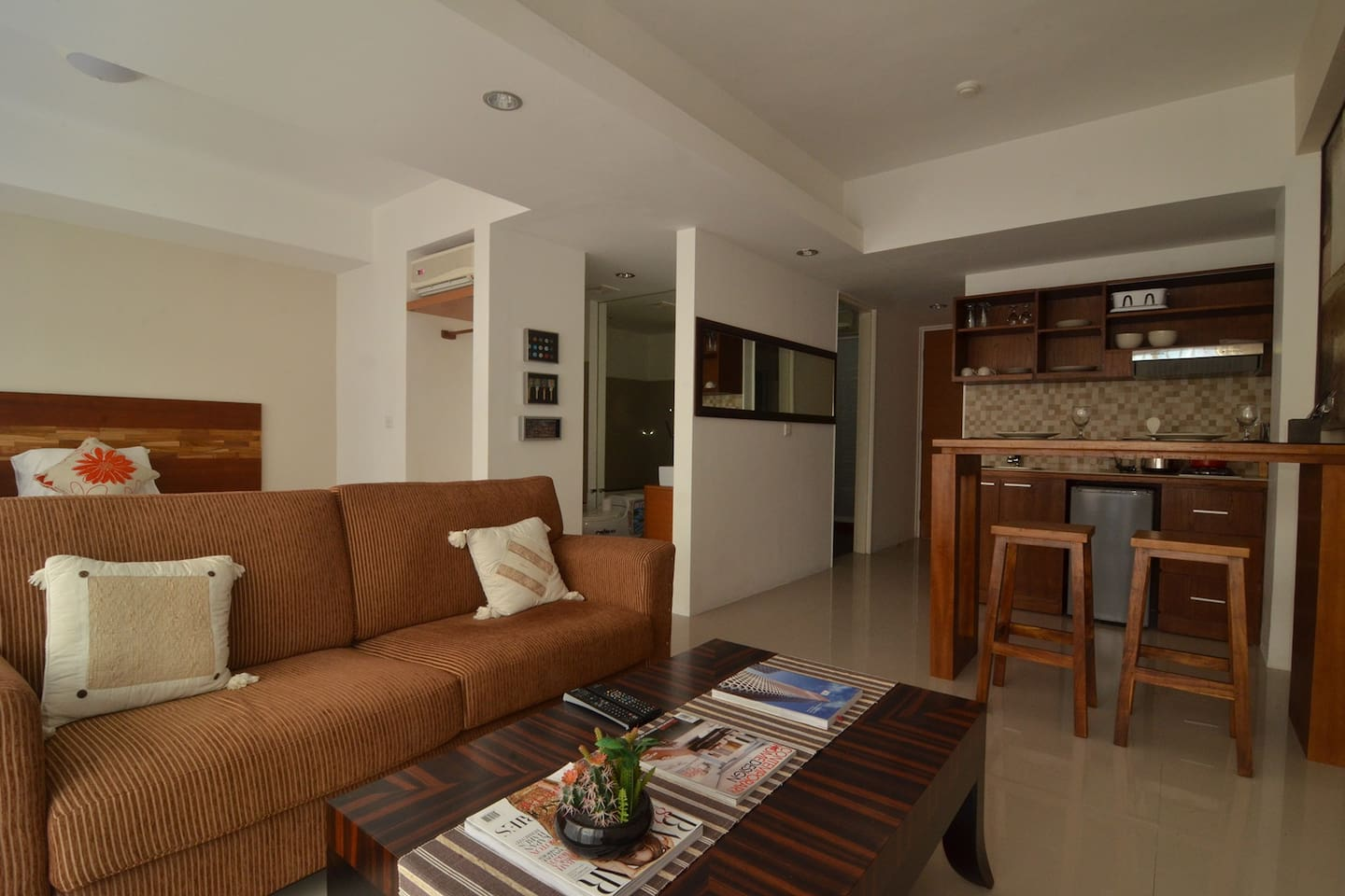 Living room, kitchen and bedroom is all an open space. The doorless bathroom is located next to the bedroom.