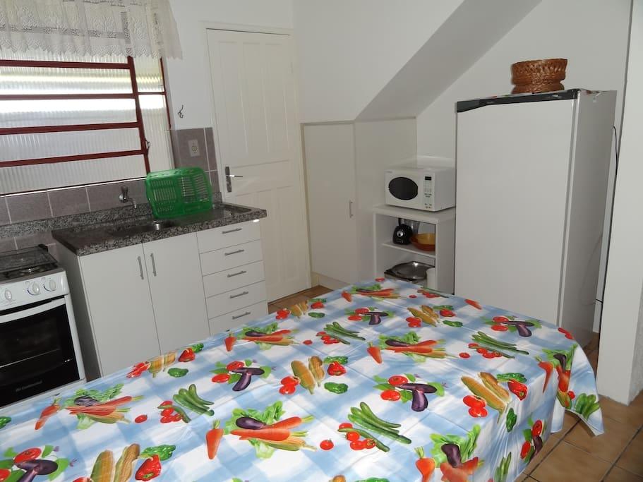 Cozinha equipada com micro-ondas, geladeira e fogão