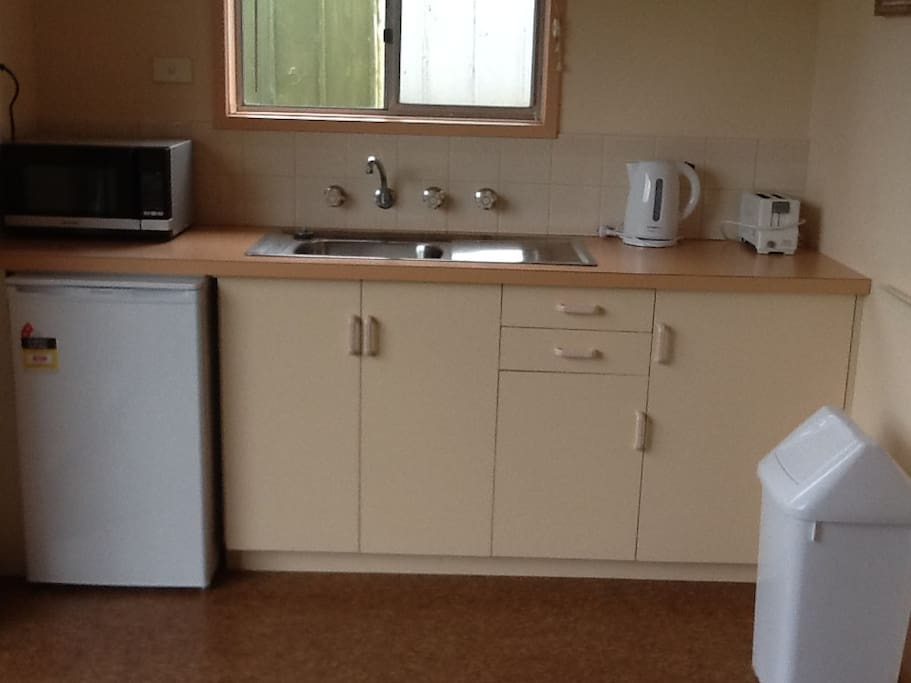 The kitchenette includes a bar fridge, toaster, kettle, microwave, cutlery and crockery.