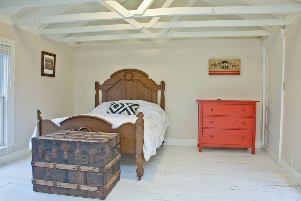 Bedroom has a queen-sized bed made up with a down comforter.  The exposed rafters make the space feel expansive in the small cottage.