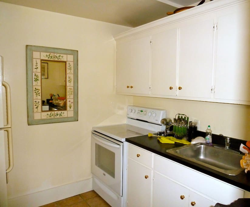 Kitchen has full size stove and refrigerator, microwave, dining, cookware and appliances.
