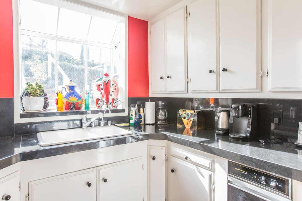 The bright kitchen with light coming in through the large windows.
