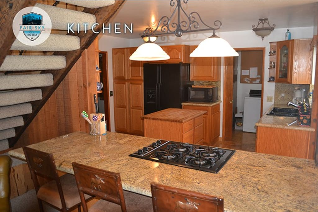 Granite counter top with 4 burner gas stove and bar stool eating, microwave, side by side refrigerator, pantry