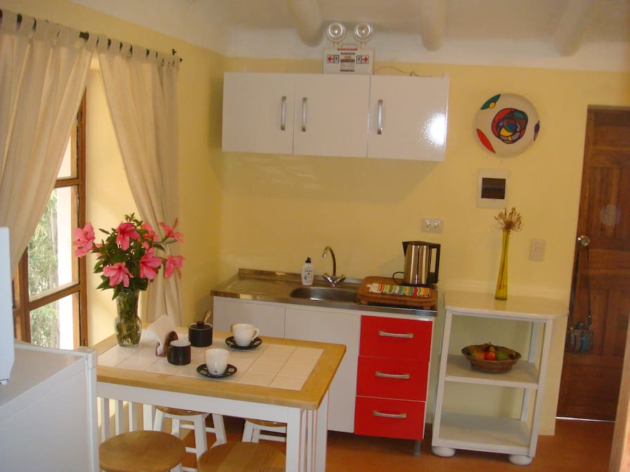 Guest Apartment. Convenient dining and kitchen area with stove, refrigerator, microwave, with dishware.