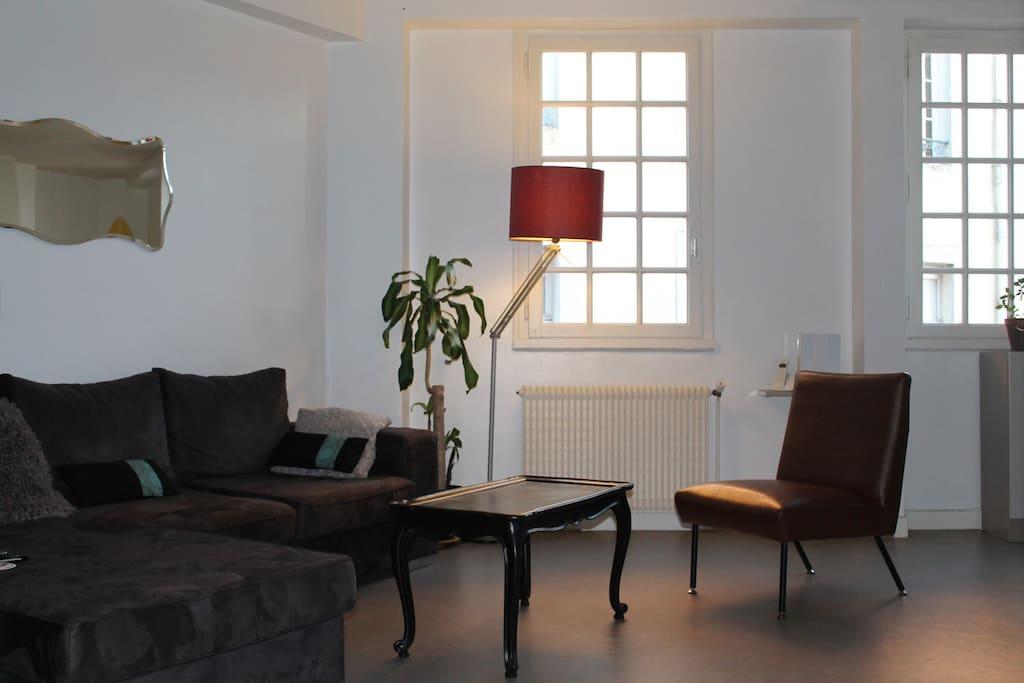 Salon-séjour lumineux donnant sur la place.
