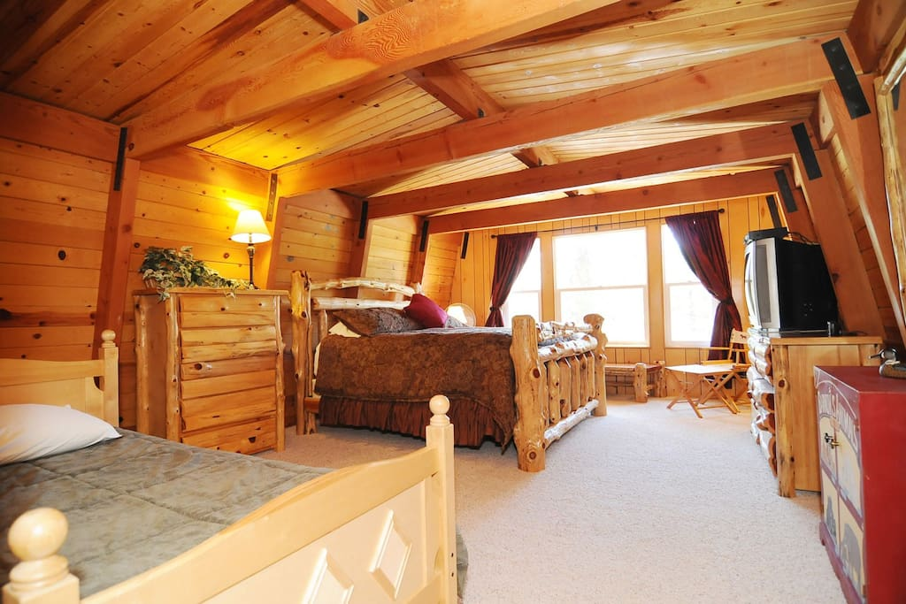 Huge Master Bedroom with King Size Log Bed and additional Queen Bed.