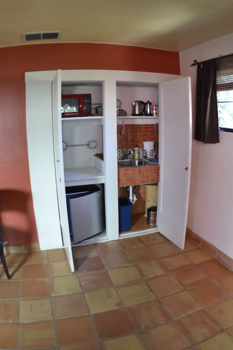 A small galley kitchenette with a microwave and refrigerator. We supply service ware, coffee/ tea service, and we recycle trash.