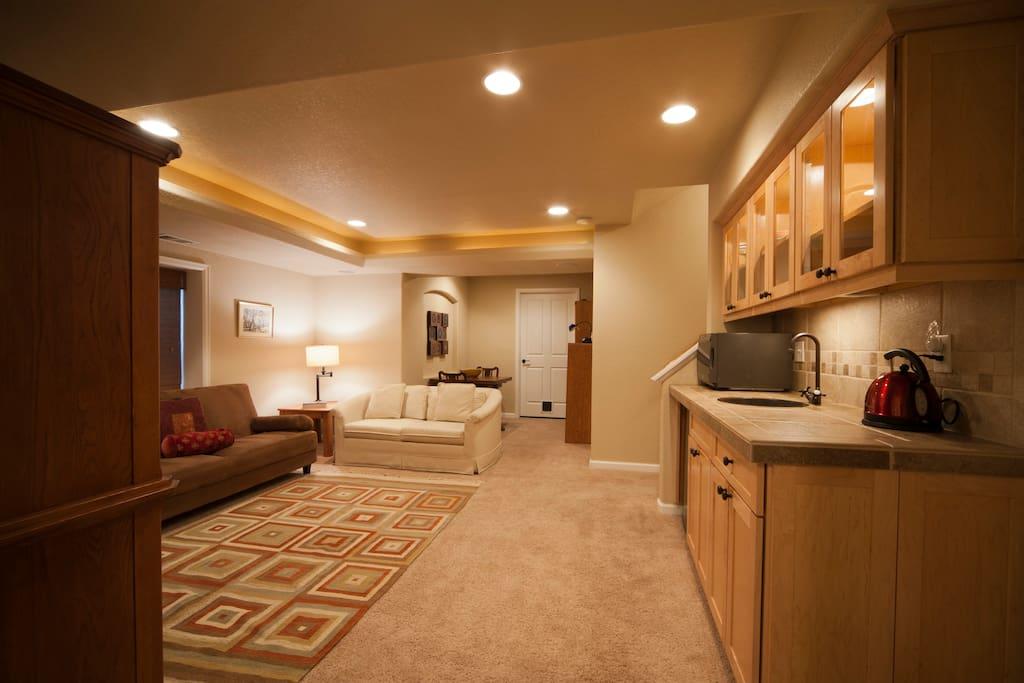 Living room from bedroom; kitchenette to right, microwave, mini-fridge, tea kettle, eating area