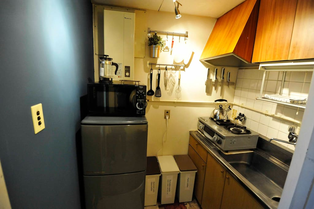 Kitchen with appliances including refrigerator, microwave, toaster, hot water pot, etc.