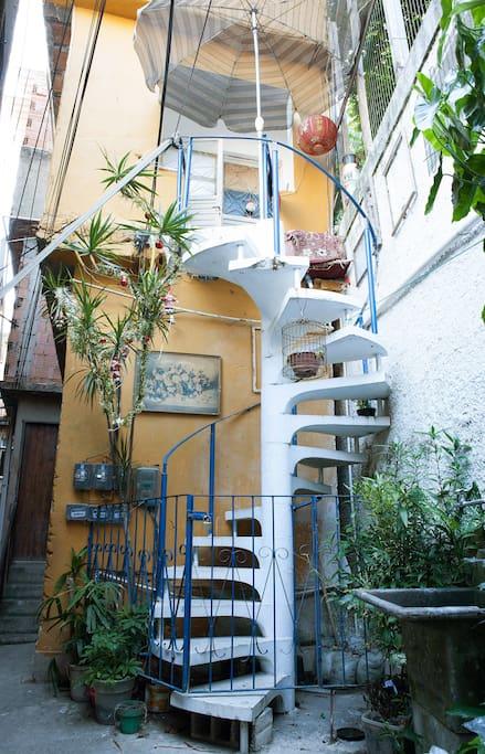 Frente da  casa com escada caracol mais quadros e plantas.