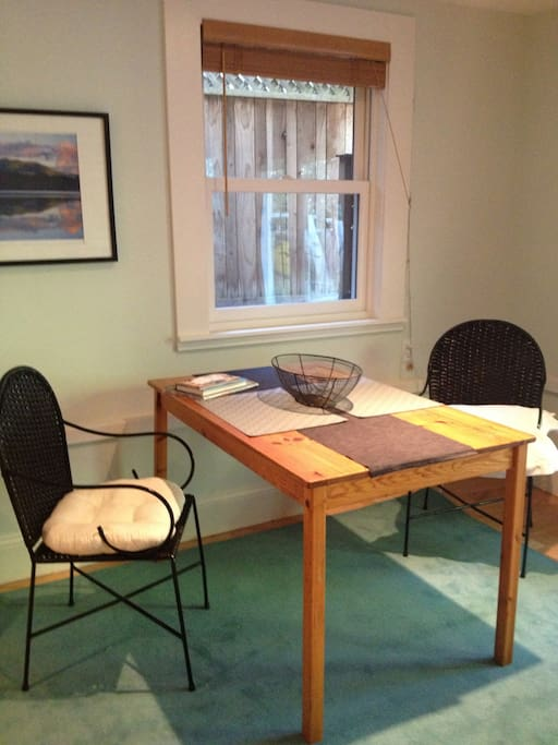 Bright and comfortable dining area, with all dishes and table linens supplied.  Some guests have put their laptops here, using it as a desk,  while looking into the garden.