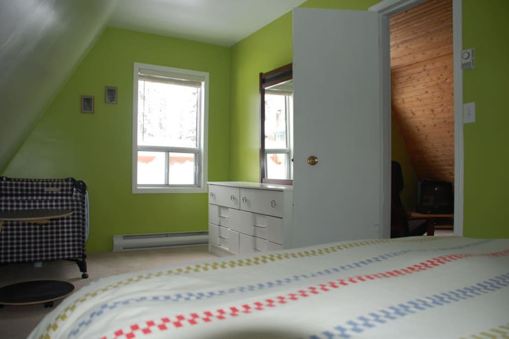 Bedroom with queen-sized bed and playpen.