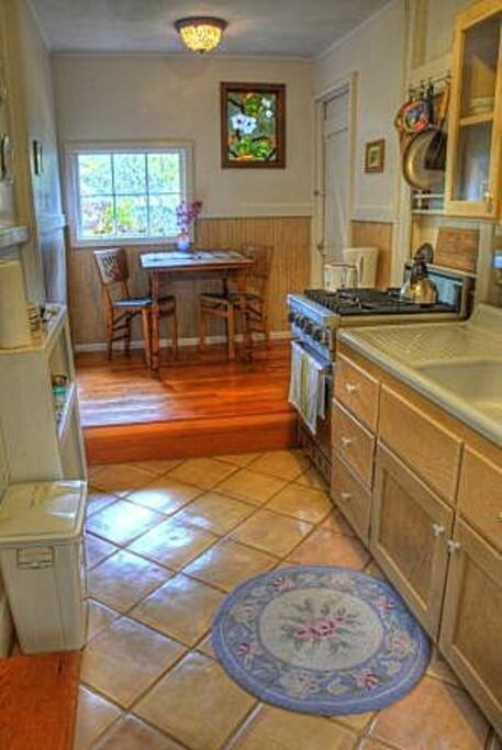 The kitchen with raised dining area and four burner gas stove.  The refrigerator is not full sized.  The inside door to the laundry room is visible at upper right.