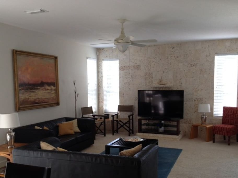 Spacious lounge with comfortable seating and huge HDTV