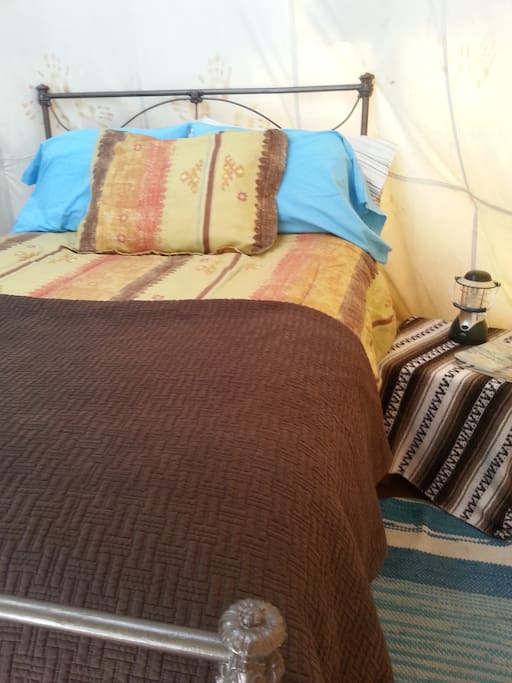 Antique iron bed with plenty of blankets for a cozy night's sleep