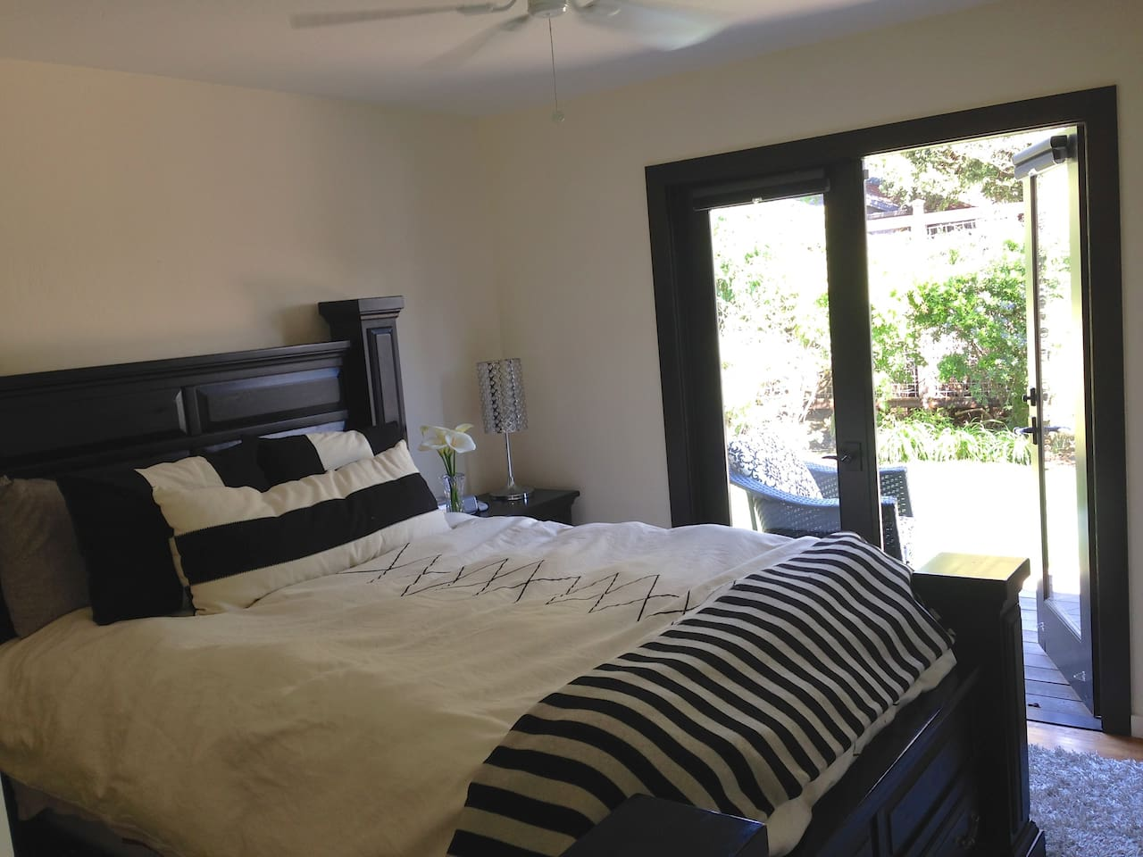 Master bedroom with French doors to backyard deck with wall mounted flat screen TV