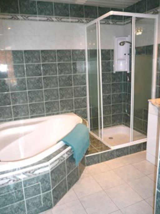 Full bathroom with corner bath.