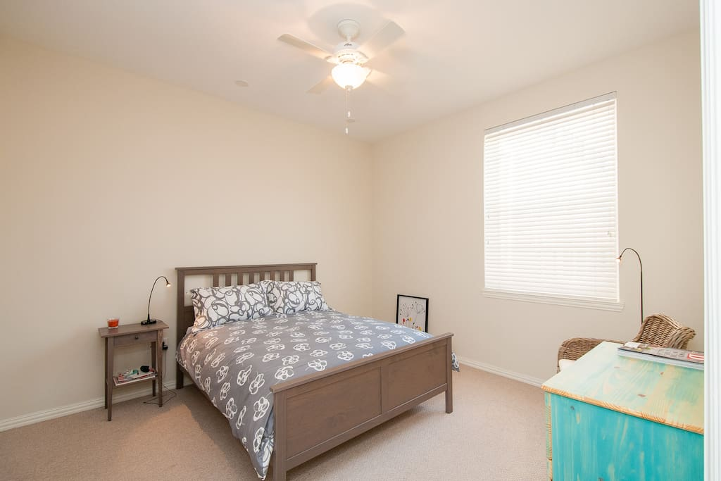 Guest Bedroom with Queen size bed, drawer and chair. There is also a private walk in closet