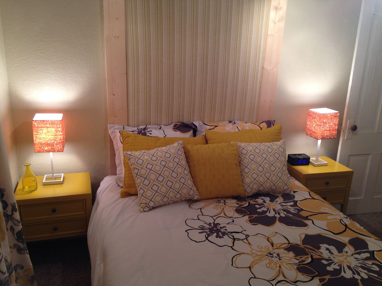 Luxe plush bedding with custom headboard and coordinating pillows.