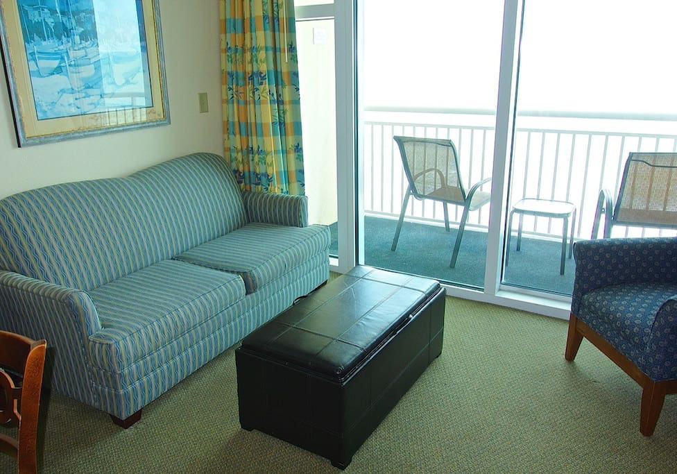 Bright and airy living room with a gorgeous direct oceanfront view has a full size sleeper sofa.