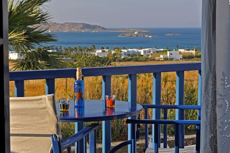 The Sea View Studio is ideal for 2 people, surrounded by a lush garden, facing a beautiful view of the Aegean Sea & the bay of Naoussa. Swimming Pool & Traditional Home-made breakfast.  BBQ Daily Maid service Laundry Service Portable / Baby bed