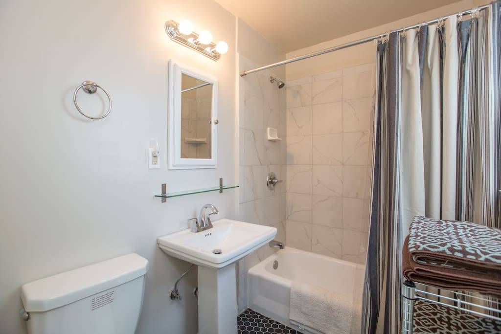 Bathroom with shower/tub featuring newer ceramic tiles, tall shower head, and built-in shelves to store your shower items.