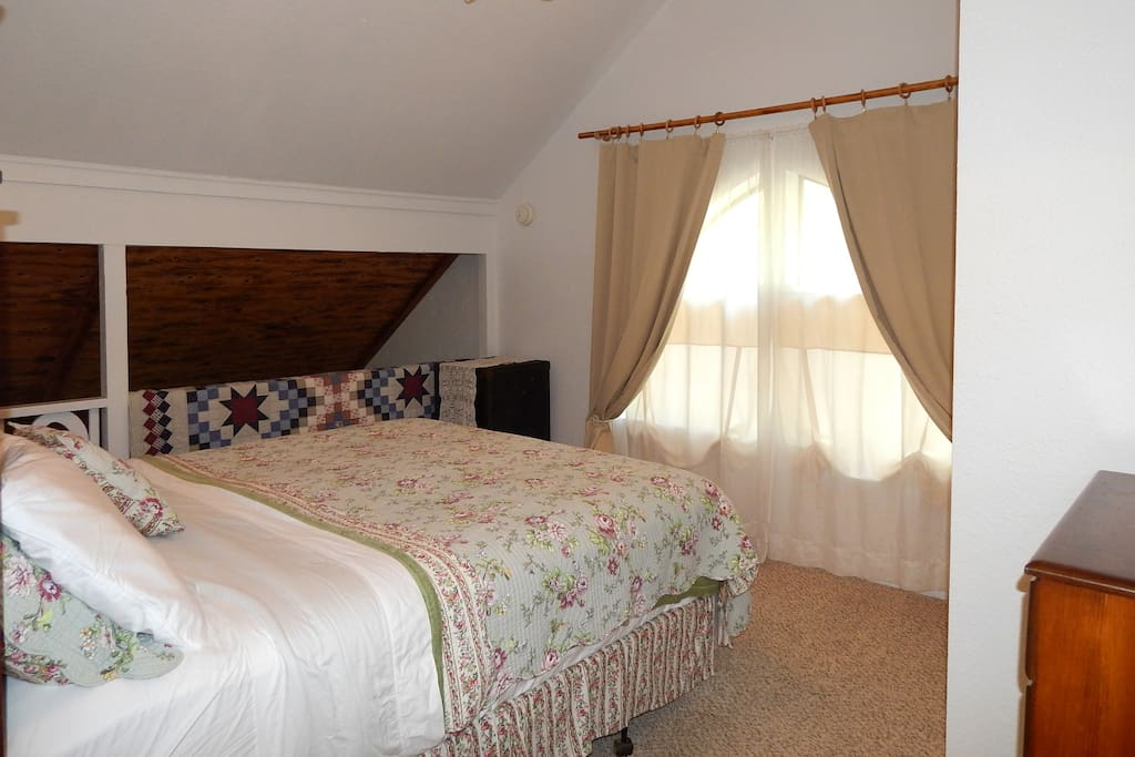 Master bedroom is light and bright with a large picture window and black out curtain for late sleepers.