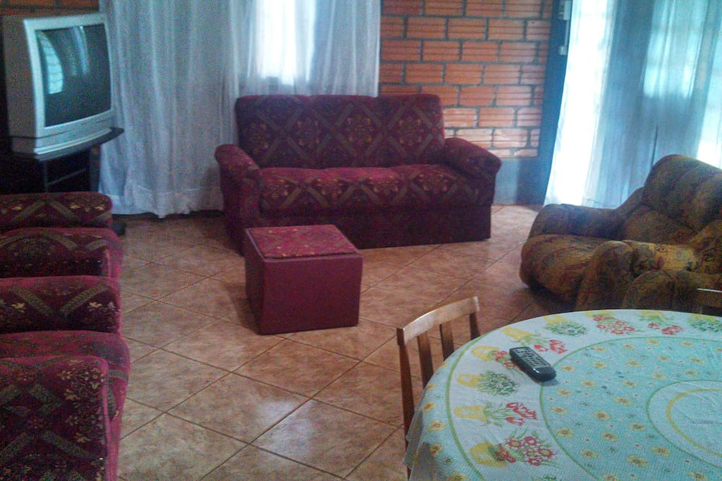 Sala con: tv a cable, sofás, mesa y sillas