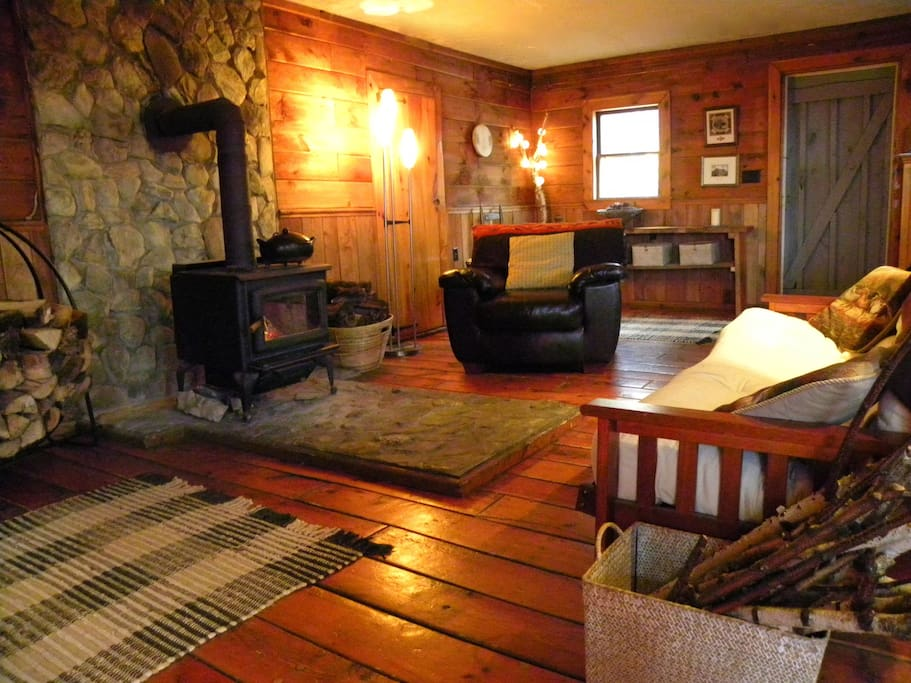 Birch Cabin main room with woodstove and stunning pine floors