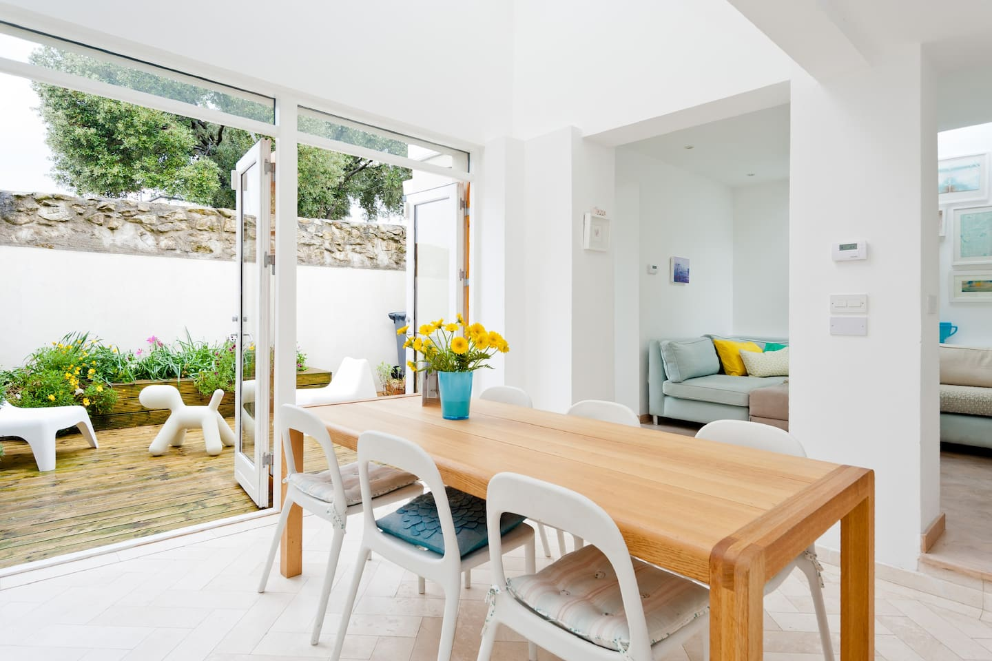 Glass doors to courtyard that completely open up the back wall of the house for a bright and airy indoor/outdoor room in summer.