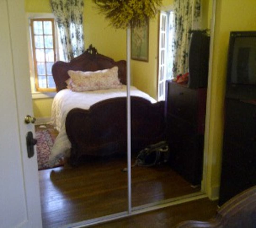 charming  bedroom with antique French bed new full sized mattress and feather bed seen thru mirrored closet wall