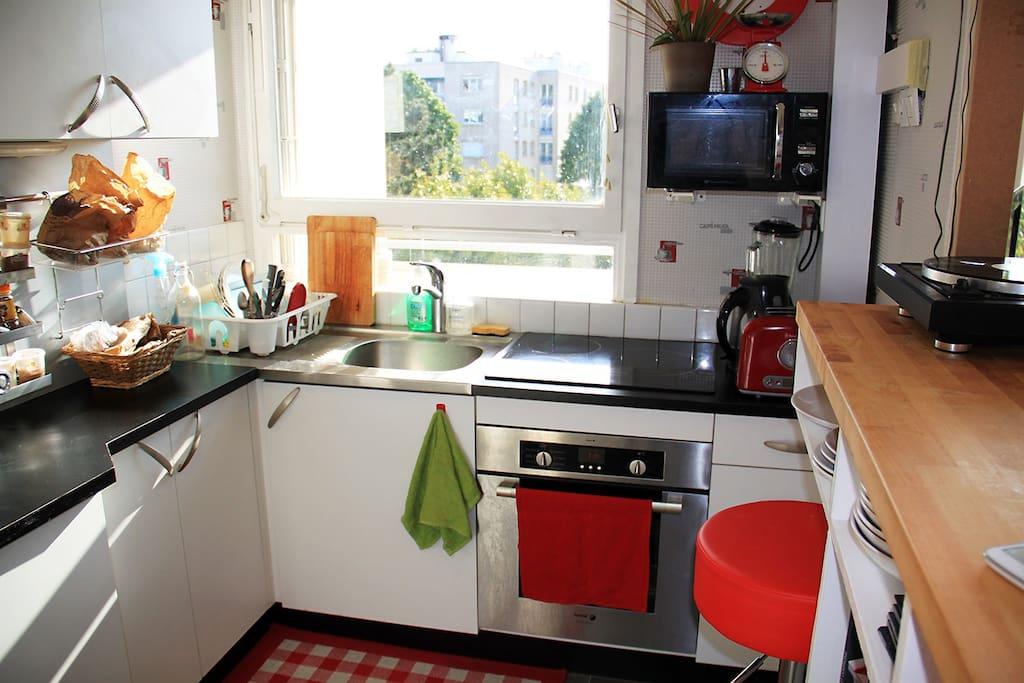 La cuisine ouverte sur le salon avec son bar/espace repas.