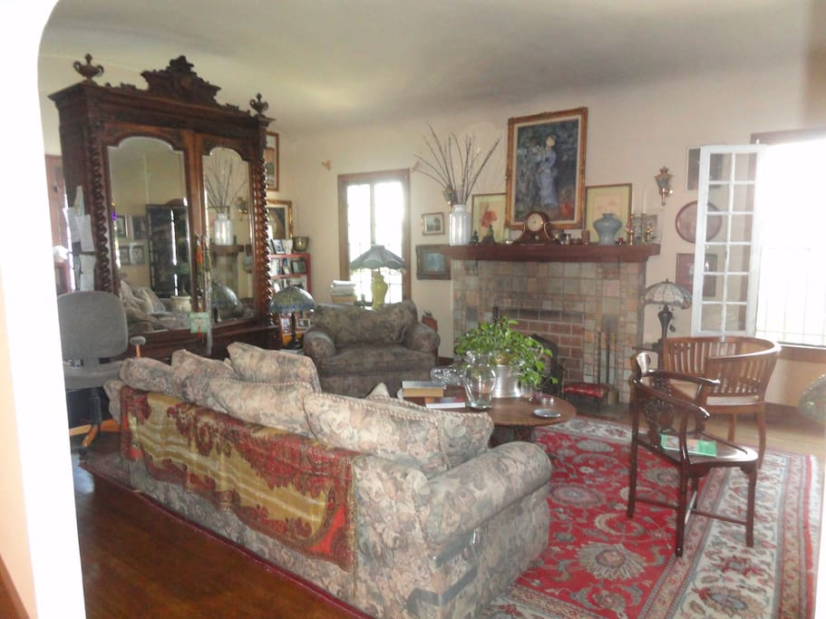 living room with batchelder fireplace and barrel ceiling