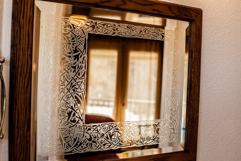 Detail of the etched mirror in the fully tiled bathroom.