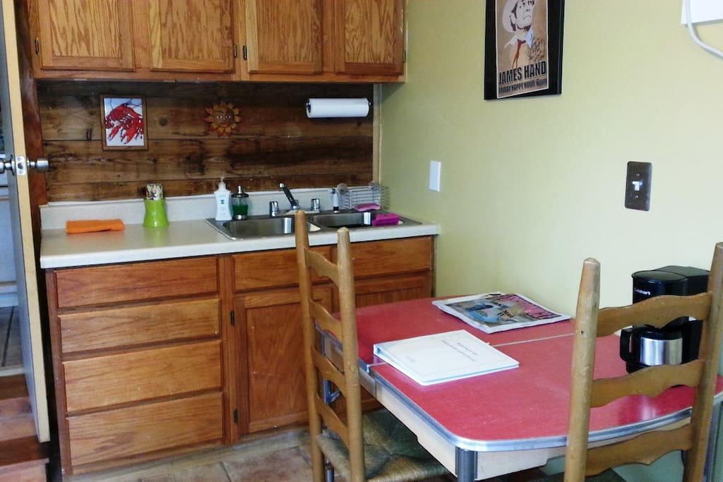 Kitchenette has a small dining table, mini fridge, microwave and coffee pot.
