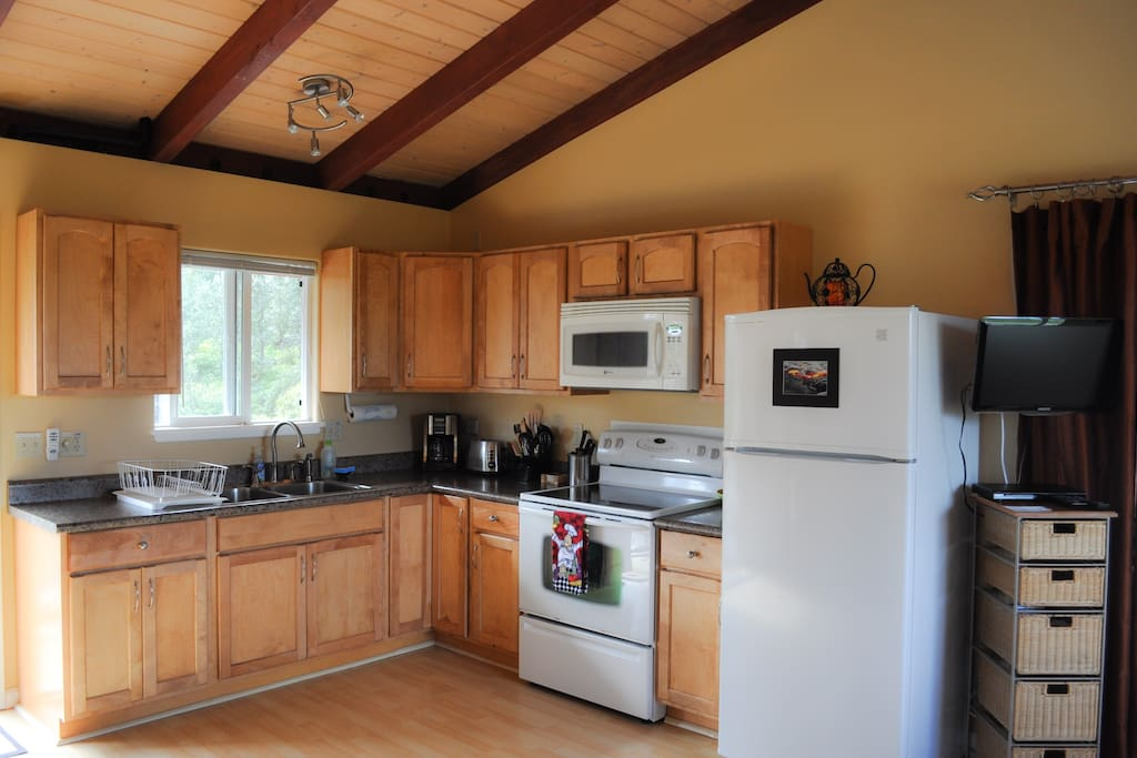 A full kitchen, with maple cabinets, fully equipped for cooking.