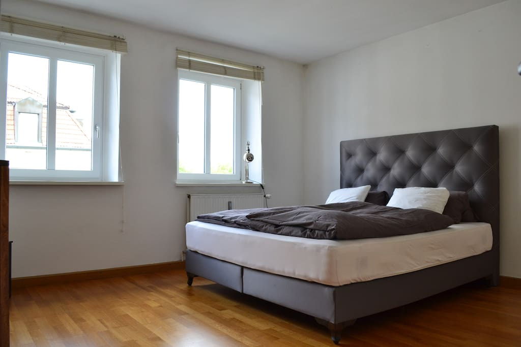 Bright bedroom with a  5 star king size luxury boxspringbed and a flat screen television