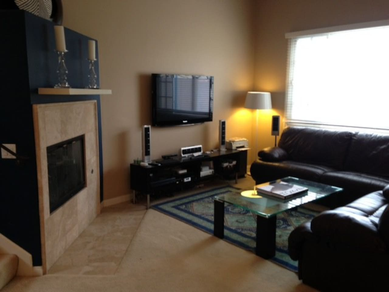 Two large plama televisions and comfortable reclining couches with two fireplaces.