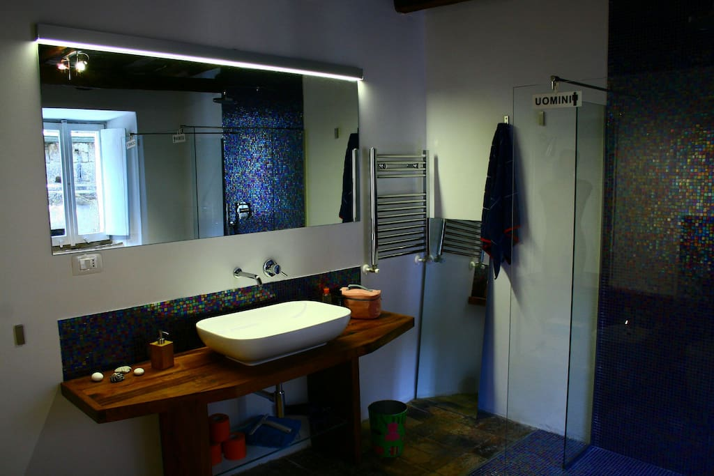 IL LAVABO bathroom: a large mirror, handmade chestnut wood top, design sink, mosaic, original cotto on the floor