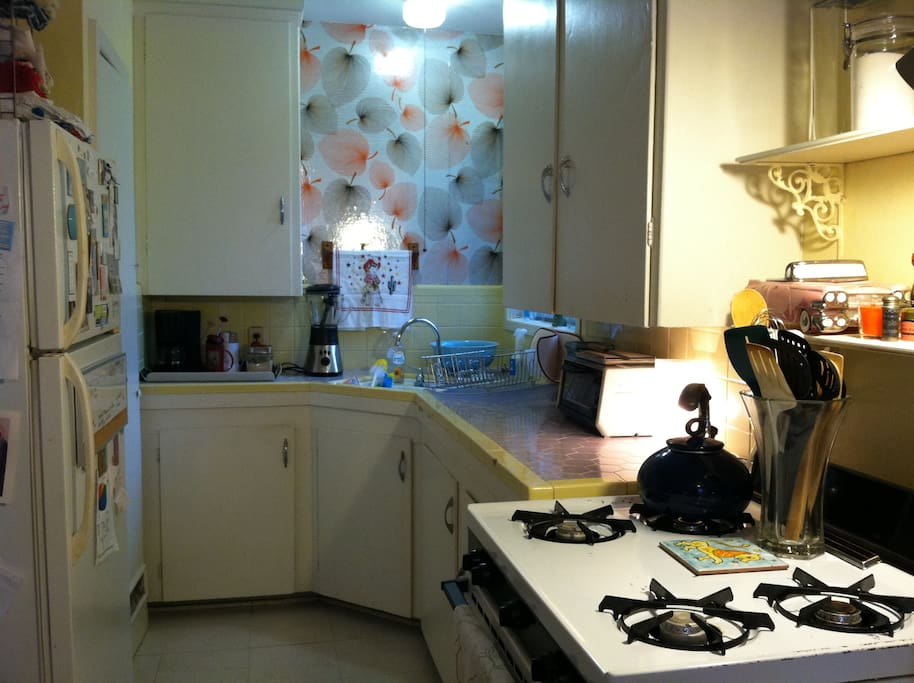 Full kitchen with stove, oven, microwave, fridge, dishes, and pots & pans.