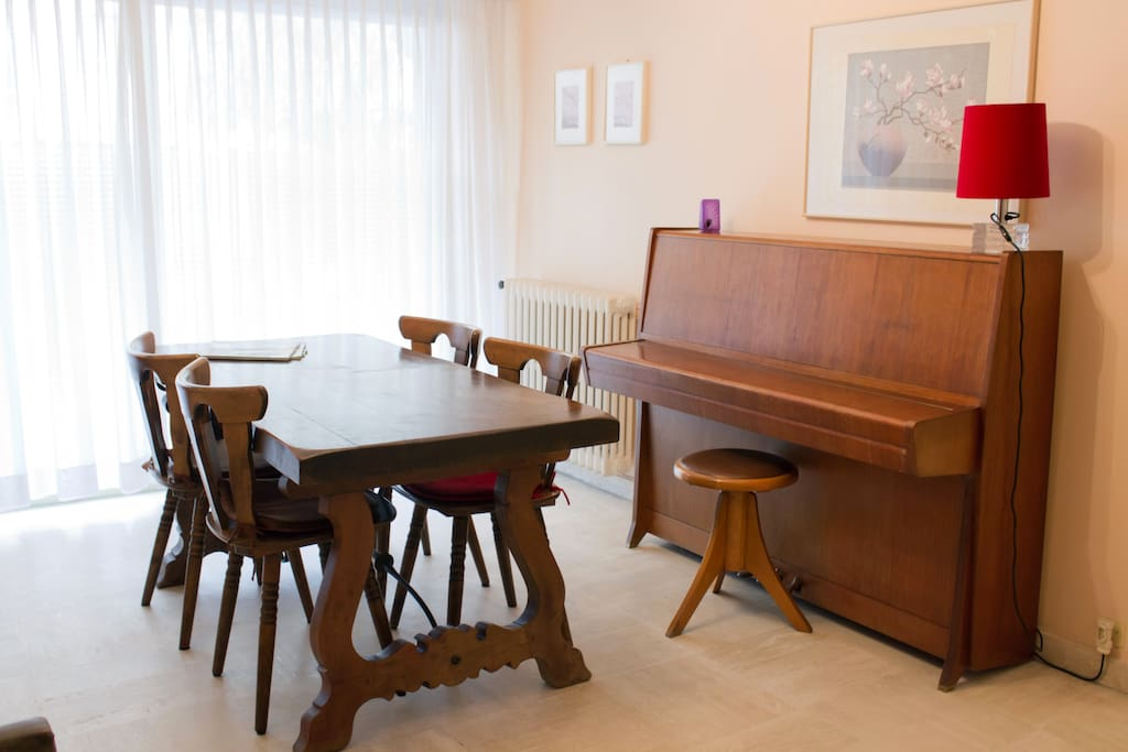 Living room with dining table, piano and window to garden behind