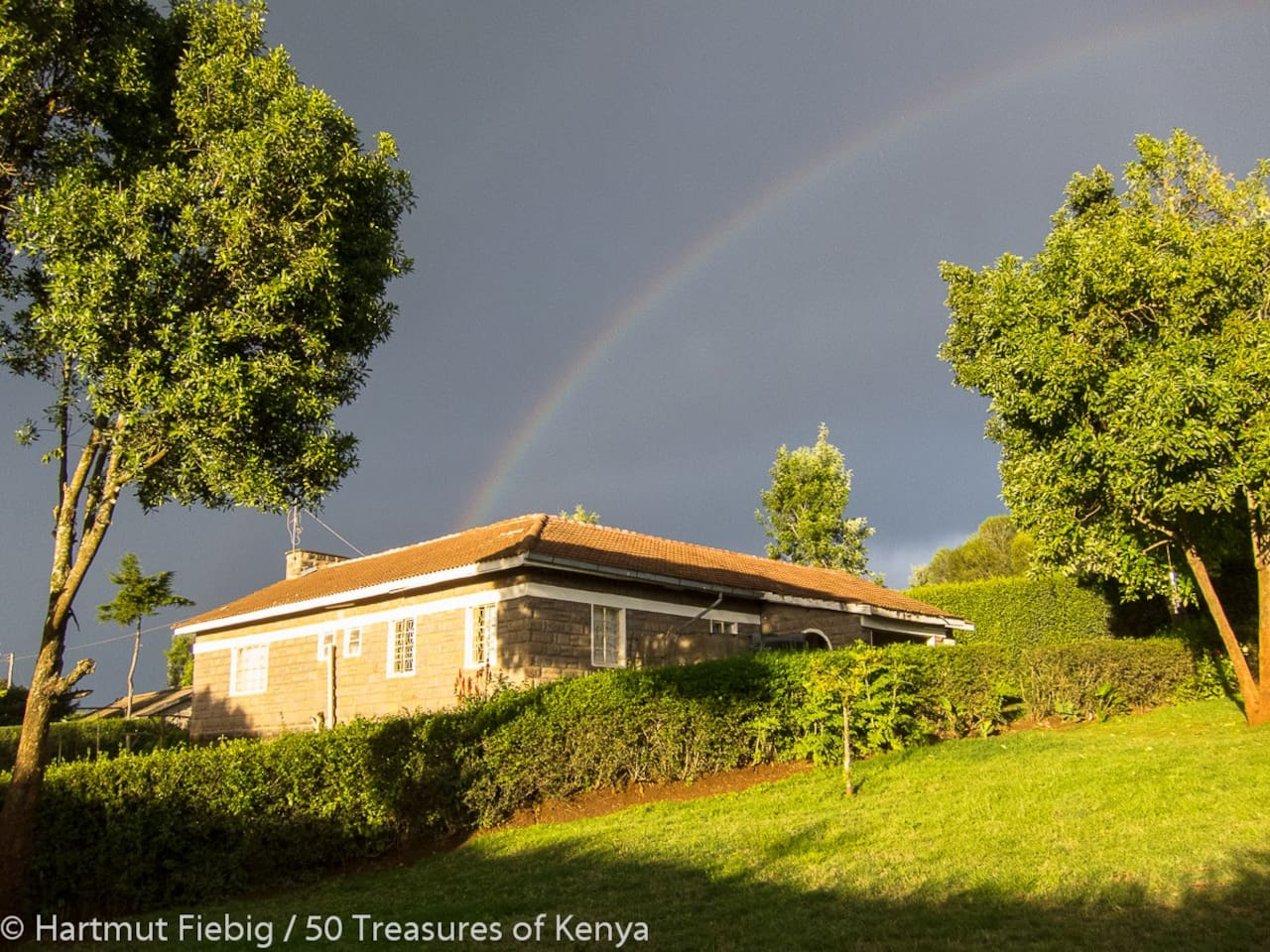 Hazina House and some of our avocado trees seen from the garden - graced by the kiss of a rainbow.