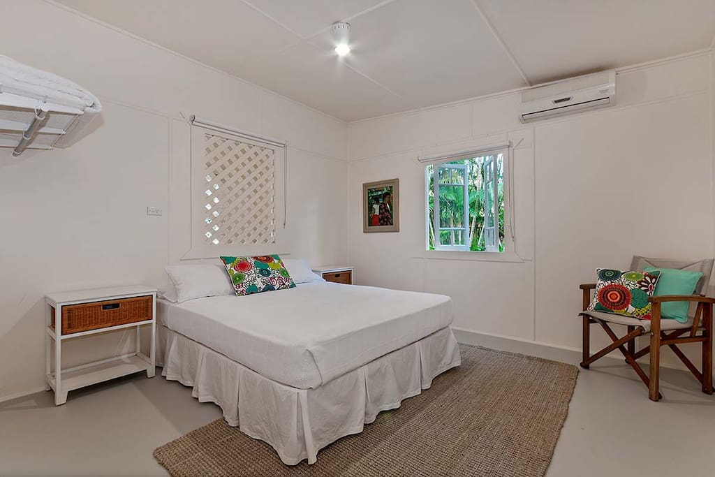 Queen bedroom with white crispy bed linen, block out blinds and airconditioner.