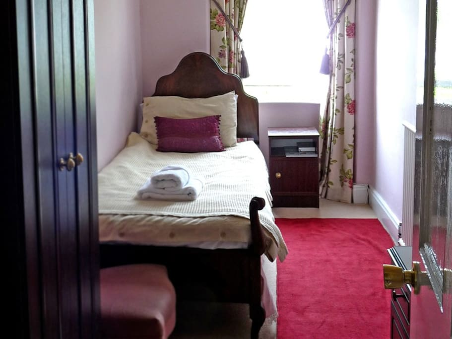 Brantfell, with its pretty Queen Anne bed and handmade mattress, overlooking north Lake Windermere and the fells.