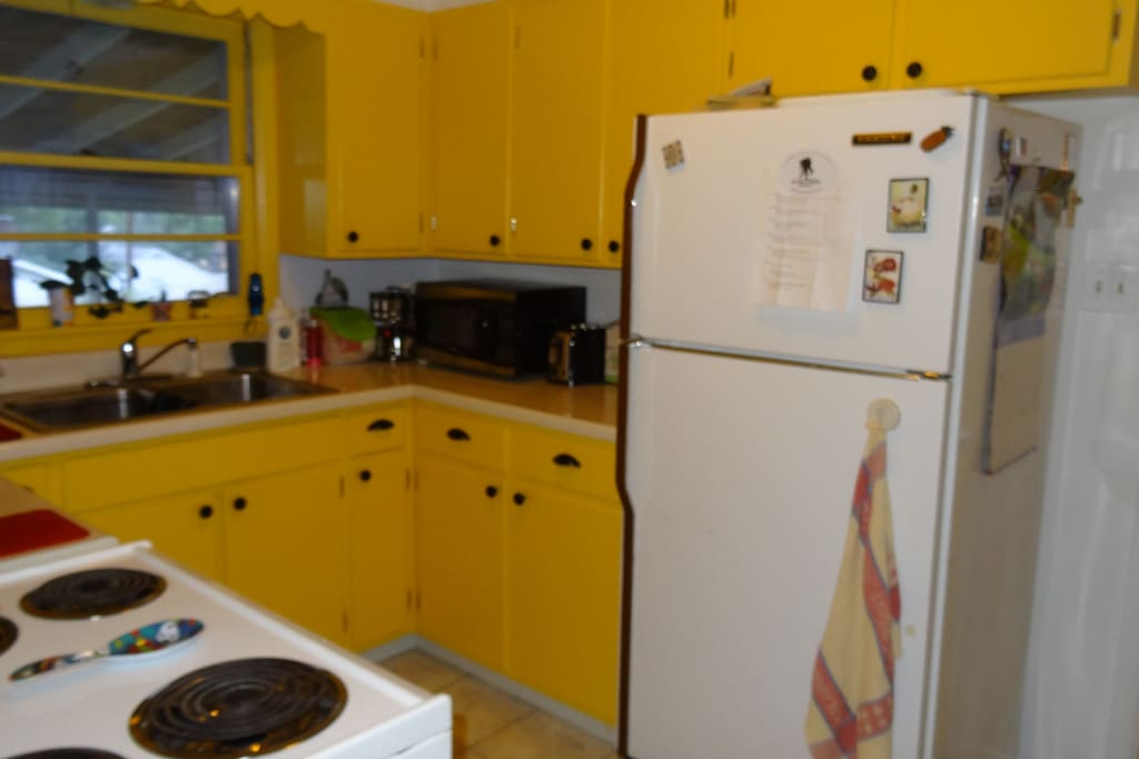 Kitchen:  electric stove and oven, refrigerator, microwave, coffee maker and dinnerware.