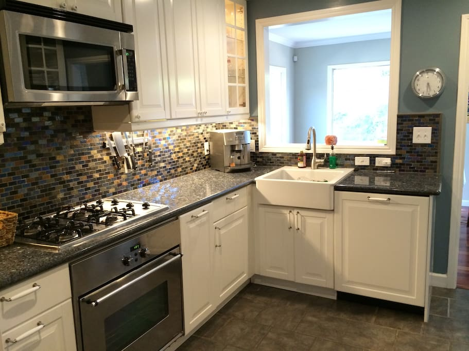 Kitchen with dishwasher, fridge, microwave, espresso coffee maker, cooking tools, etc.