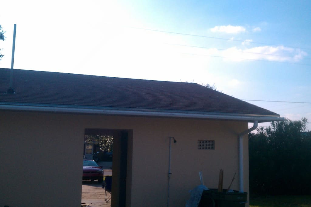 Carport and Main entrance, open to back yard with outside shower head and Shed