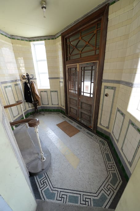The Entrance to the apartment, complete with original Victorian tiling on wall and floor.