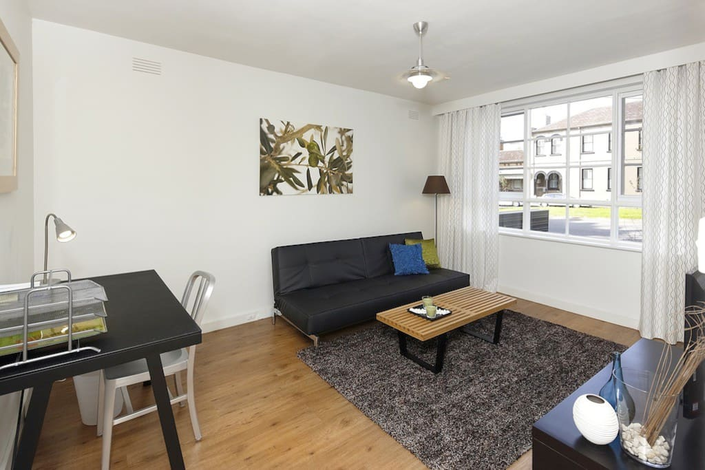 Spacious, stylish living room with sofa (converts to king single bed), high-def digital TV, work desk and secure balcony (not shown).